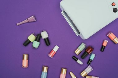 top view of scattered nail polishes and uv lamp isolated on purple