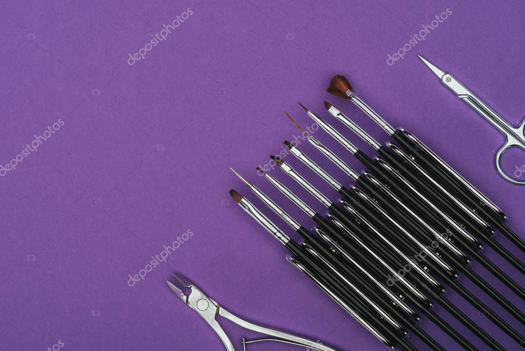 top view of brushes, scissors and nail nippers isolated on purple