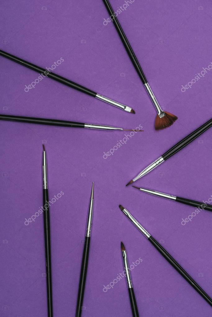 top view of scattered brushes isolated on purple