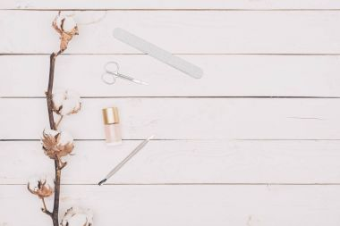 top view of scissors, nail file and nail polish on wooden table