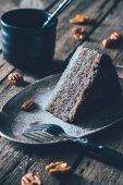 Chiuda sulla vista di pezzo di torta fatta in casa su lastra di metallo sul ripiano del tavolo in legno