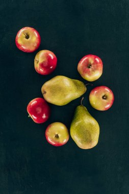top view of arrangement of fresh pears and apples isolated on black