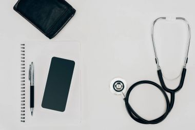 top view of medical stethoscope, notebook and smartphone on white surface