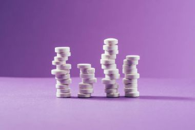 close up view of arranged pills on purple background