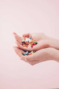 partial view of woman holding pills in hands isolated on pink