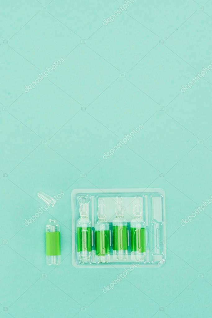 top view of arranged ampules isolated on green