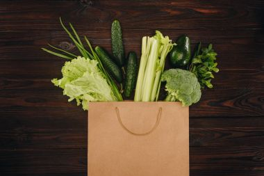 top view of green vegetables in shopping bag on wooden table
