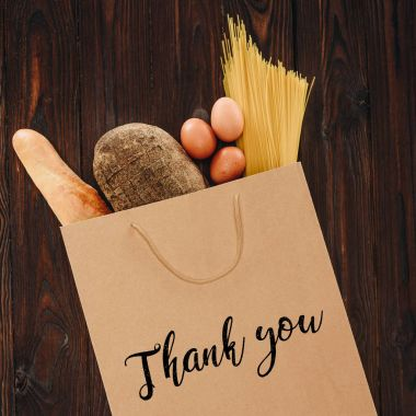 top view of bread, pasta and eggs in paper bag with words thank you, grocery concept