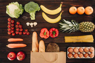 top view of vegetables and fruits, bread and eggs on wooden table, grocery concept