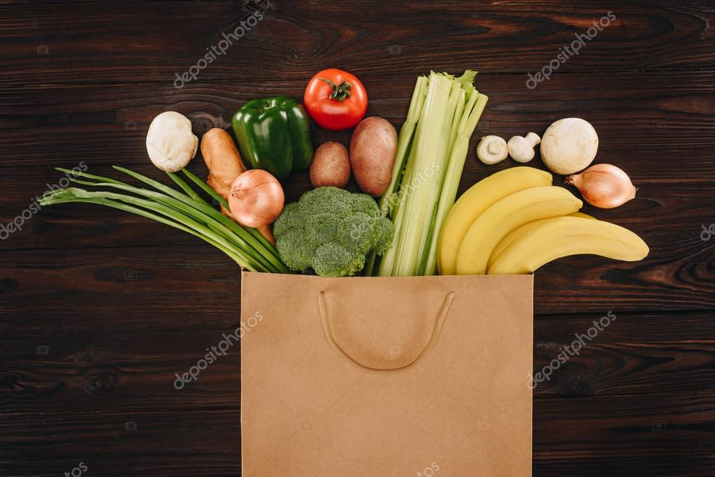 top view of different vegetables and fruits in shopping bag on wooden table, grocery concept