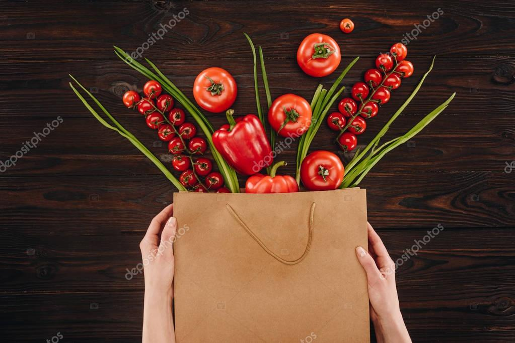 cropped image of girl holding shopping bag with vegetables on wooden table