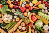 top view of vegetables and fruits with bread on wooden table