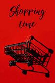 Fotografia un carrello con ombra sulla parete rossa e parole tempo di Shopping