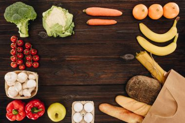 top view of vegetables and fruits with bread and pasta in paper bag, grocery concept