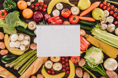 top view of empty notebook on vegetables and fruits on wooden table, grocery concept