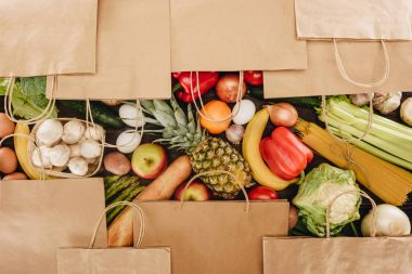 top view of shopping bags covering vegetables and fruits on wooden table