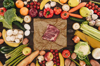 top view of piece of raw meat between vegetables and fruits on wooden table