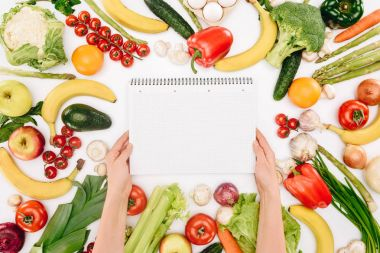 cropped image of girl holding notebook between vegetables and fruits isolated on white