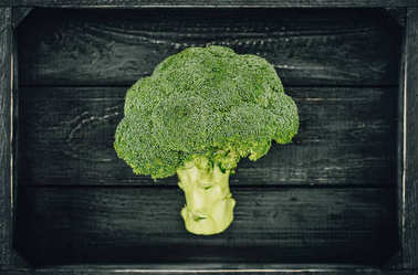 top view of green ripe broccoli in wooden box
