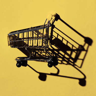 one shopping cart with shadow on yellow wall