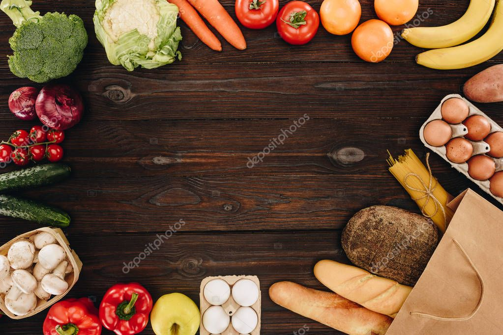 top view of vegetables and fruits with bread and pasta on wooden table, grocery concept