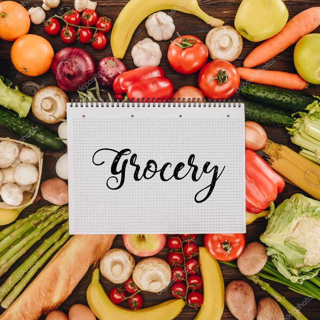 top view of notebook with word grocery on vegetables and fruits on wooden table