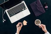 abgeschnittene Aufnahme einer Geschäftsfrau, die Kaffee trinkt und am Arbeitsplatz zeichnet, isoliert auf schwarz