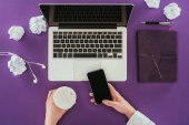 cropped shot of businesswoman using smartphone and drinking coffee at workplace on purple surface