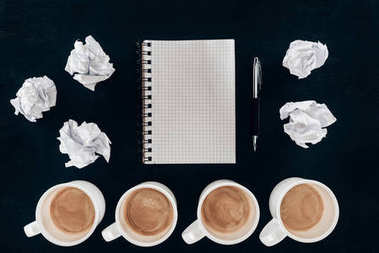 top view of blank notepad with messy crumpled papers and cups of coffee in row isolated on black