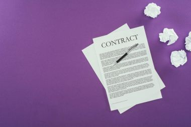 top view of business contract with pen on purple surface