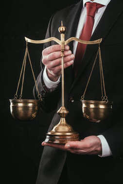 cropped shot of lawyer holding justice scales isolated on black