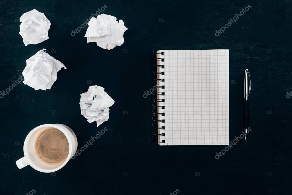 top view of blank notebook with messy crumpled papers and cup of coffee isolated on black