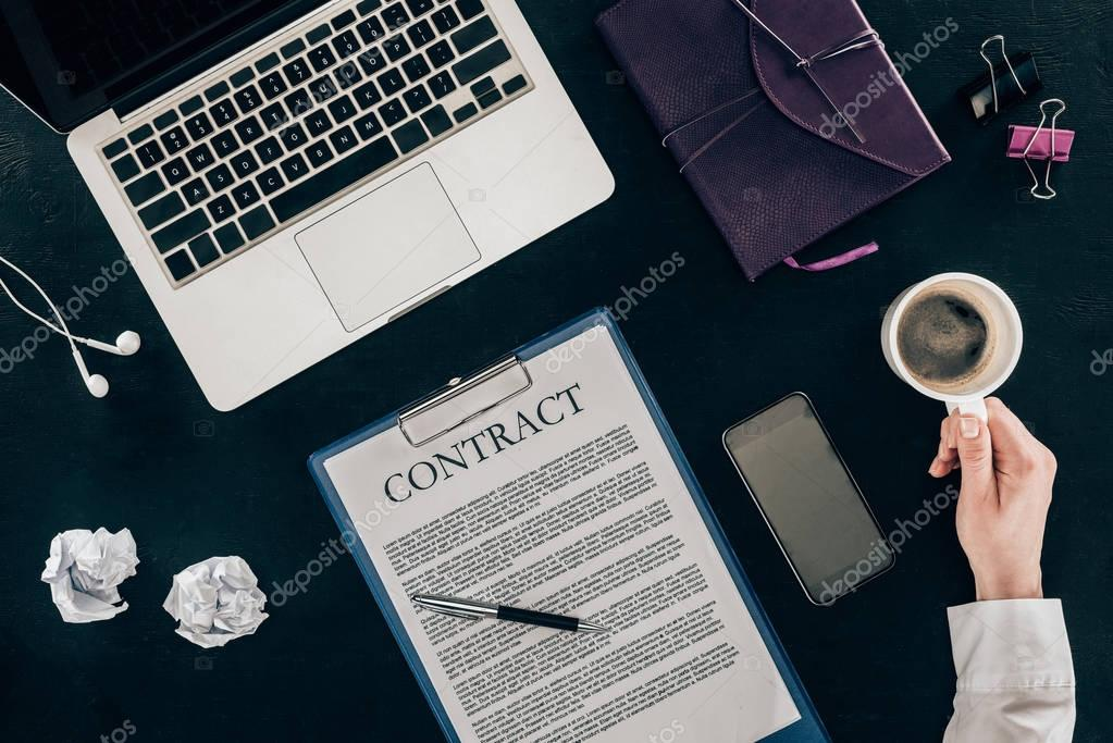 cropped shot of businesswoman drinking coffee at workplace with contract isolated on black