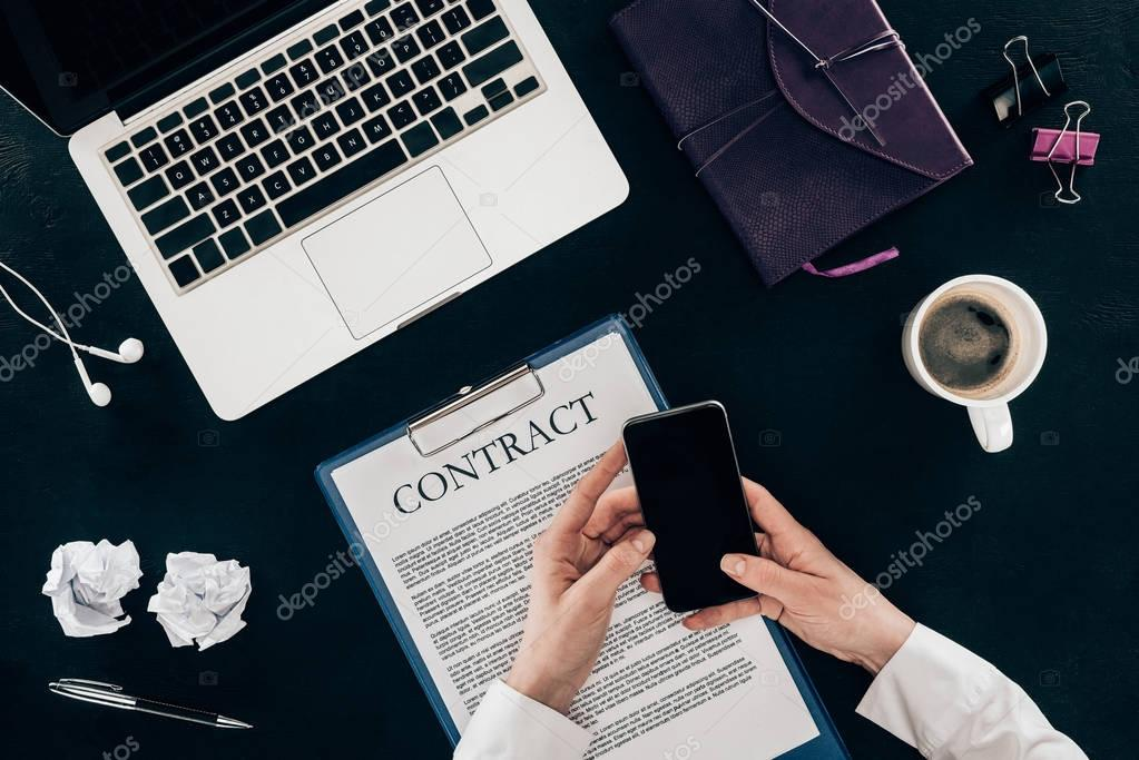 cropped shot of businesswoman using smartphone at workplace isolated on black