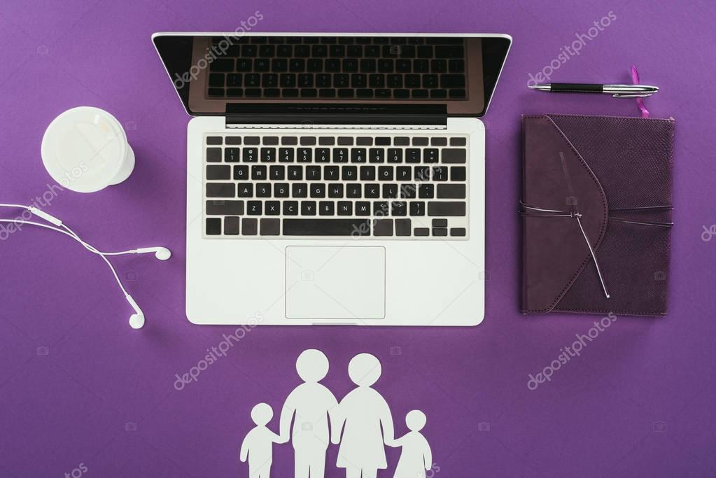 top view of business workplace with cut out family figures on purple surface, family insurance concept