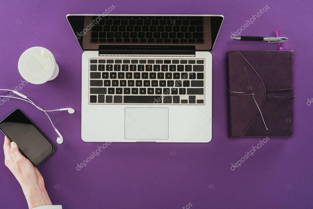 cropped shot of modern businesswoman using smartphone at workplace on purple surface