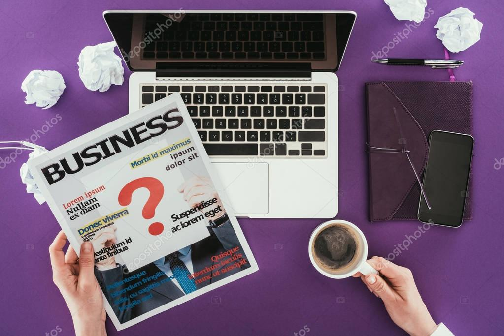 Cropped shot of businesswoman reading magazine at workplace on purple surface