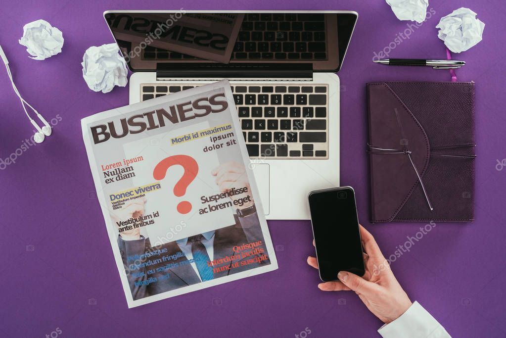 cropped shot of businesswoman using smartphone at workplace on purple surface