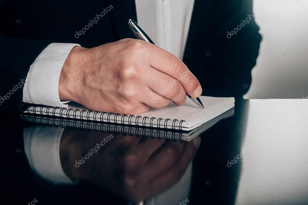 cropped shot of businessman writing in notepad