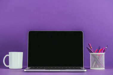 workplace with laptop and coffee mug on purple surface