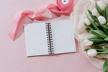 top view of notepad, pink ribbon and white tulips for international womens day