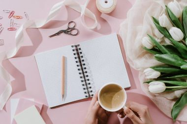cropped view of woman holding coffee cup on pink surface with tulips and notepad