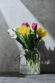 Fotografie spring tulip flowers in glass jar on concrete surface with shadow