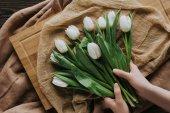 Fotografie oříznutý pohled ženy s kyticí tulipánů na ubrus a dřevěné tabule pro 8 březen
