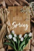 Fotografie pohled shora bílých tulipánů na dřevěné desce s hello jarní nápis