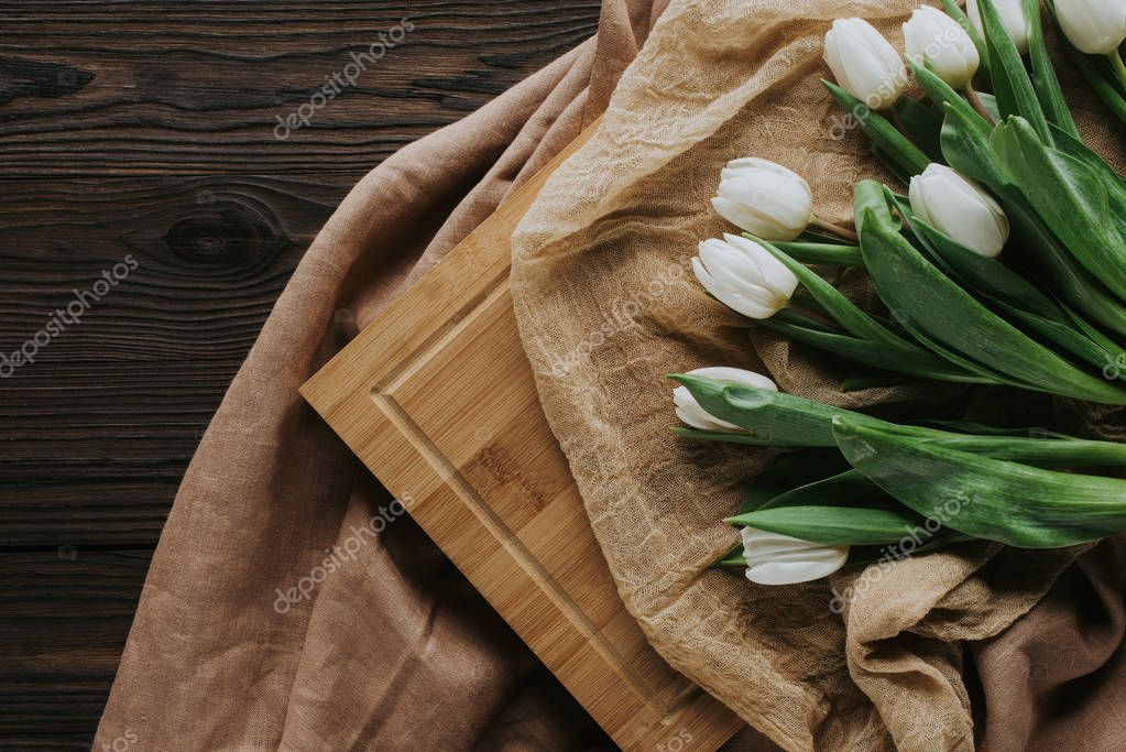 top view of spring tulips on tablecloth and wooden board for international womens day