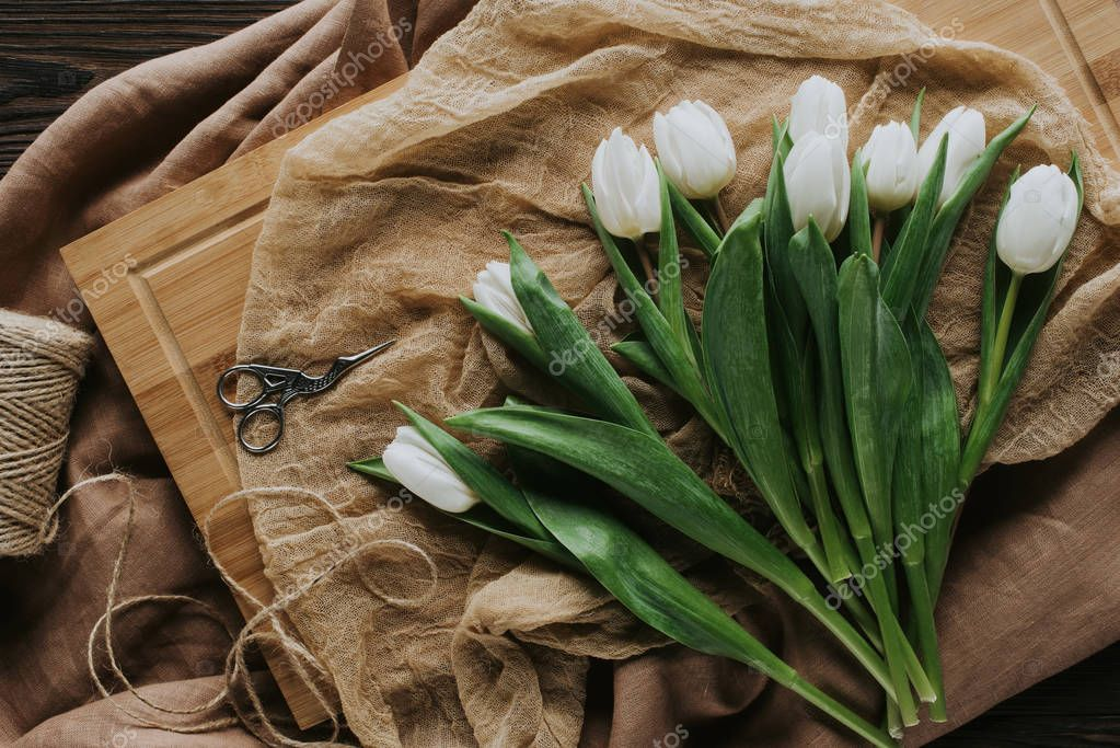 top view of white spring tulips on wooden board for international womens day