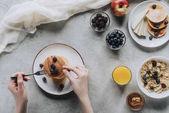 Oříznout záběr člověka jíst na snídani vynikající domácí palačinky s ovocem