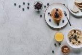 pohled shora na lahodné domácí snídani palačinky, ovoce, medu a müsli Grey