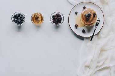 top view of sweet homemade pancakes with honey and fresh berries on grey